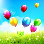 Link toGreen grass and colored balloons background