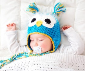 A cute baby with a cap and a pacifier Stock Photo