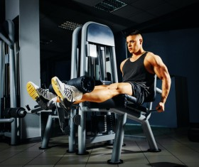 A young man doing leg exercise on equipment