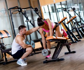 A young woman with her personal trainer working out in the Gym
