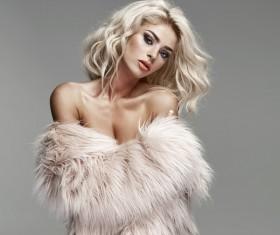 Blonde fashion model wearing fur clothes