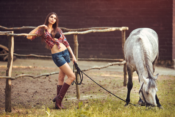 Beautiful girl holding horse and fence background