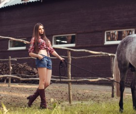 Beautiful girl holding horse and house background