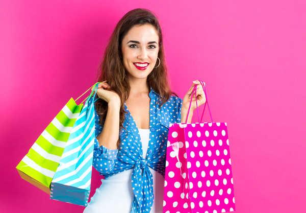 Beautiful woman holding shopping bags in pink background