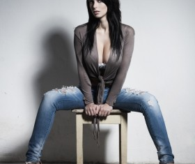 Beautiful woman sitting on a stool in gray background