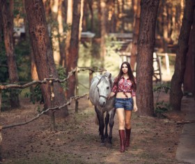 Beautiful young girl holding a white horse