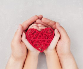 Big hand and small hands holding red weave heart-shaped Stock Photo