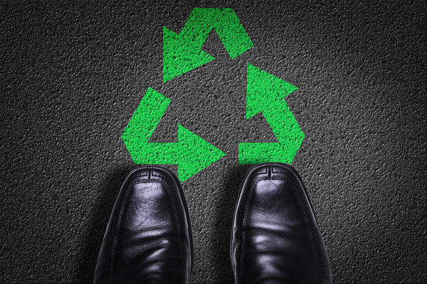 Black background shoes and green recycling logo Stock Photo