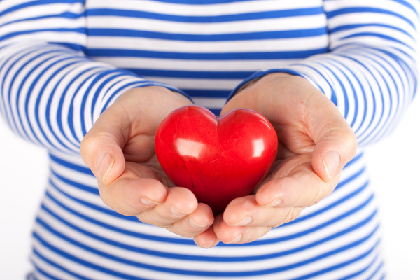 Holding a red heart shaped Stock Photo