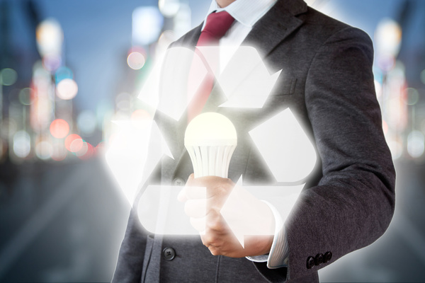 Blurred background holding a white bulb recycling symbol Stock Photo