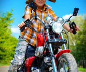 Boy riding a motorcycle with blue sky background