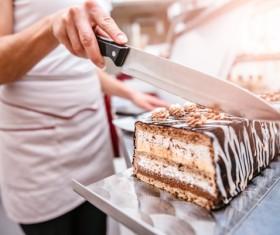 Cake maker cuts creamy chocolate cake 02
