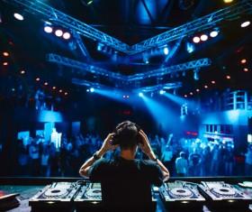 Disc jockey mixing electronic music in club people are dancing