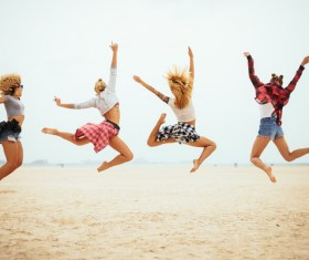 Four young girls jumping on the beach Stock Photo