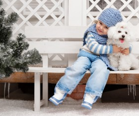 Girl sitting on a bench with white puppy Stock Photo