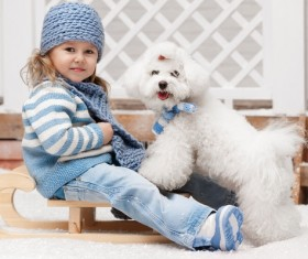 Girl sitting on a sled and white puppy Stock Photo