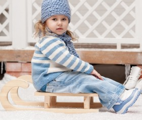 Girl sitting on a sled in winter Stock Photo