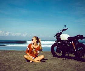 Girl sitting on the beach with a motorcycle Stock Photo