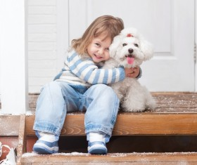 Girl sitting on the promenade with arms around white puppy Stock Photo
