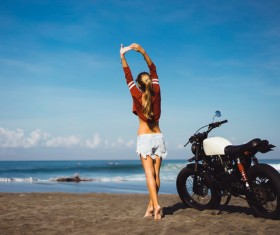 Girl stretching with arms and motorcycle Stock Photo