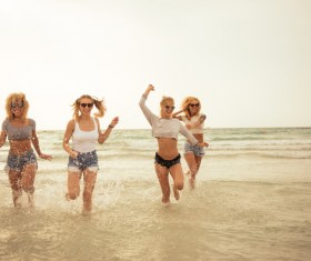 Girls wearing T blood and shorts in the sea in the joy of running