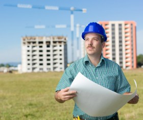 Hand drawing engineer with building crane in the background