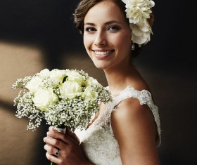Hand-held bouquet of smiling young beautiful bride