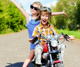 Happy kids go on a journey on a motorcycle on a bright sunny day