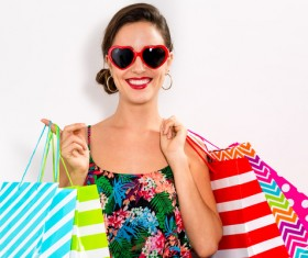 Happy woman holding shopping bags on white background