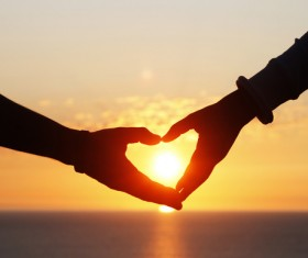 Heart shape of hands against sea during sunset Stock Photo