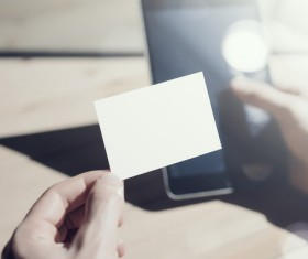 Holding a blank business card with blurred cell phone background