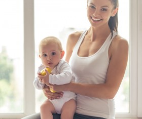Holding a yellow dumbbell baby sitting in her arms Stock Photo