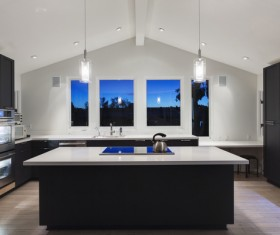 Interior of kitchen with high vaulted ceiling pendant lights white kitchen cabinetry and steel appliances