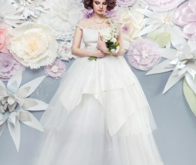 Low head holding flowers Happy woman wearing a wedding dress with fake background