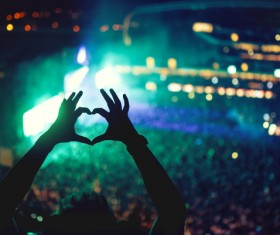 Music concert with lights and silhouette of a man partying heart