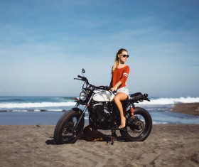 Pretty girl riding a motorcycle with a sea background Stock Photo