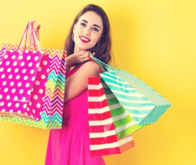 Pretty happy woman holding shopping bags on a yellow background