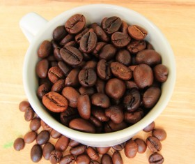 Small bowl of coffee beans wooden desktop photo