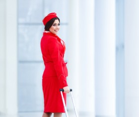 Smiling flight attendants dragging the suitcase turned Stock Photo