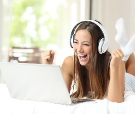 Smiling girl with white headphones and laptop lying in bed Stock Photo