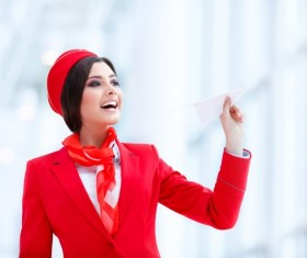 Smiling stewardess holding paper airplane Stock Photo