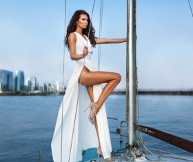 Standing on the bow dressed in a beautiful white dress dignified woman fashion photos