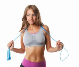 Stock Photo Young woman exercising with rope skipping
