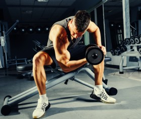Strong muscular bodybuilder doing exercise with dumbbell in the gym