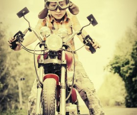 The boy riding a motorcycle with fuzzy background