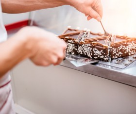 The cake maker who is taking the chocolate cake Stock Photo