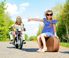 The fashionable girl asked to ride with a boy riding a motorcycle Stock Photo
