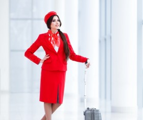The young flight attendant with a suitcase at the airport Stock Photo