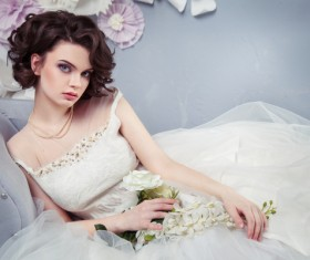 Woman wearing a wedding dress holding flowers sitting on the couch