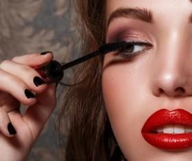 Women with red lips brush eyelashes